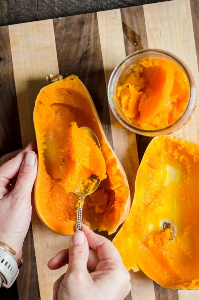 A butternut squash cut on in hand on a cutting board. A person is using a spoon to scoop out the cooked flesh from the skin of the squash.