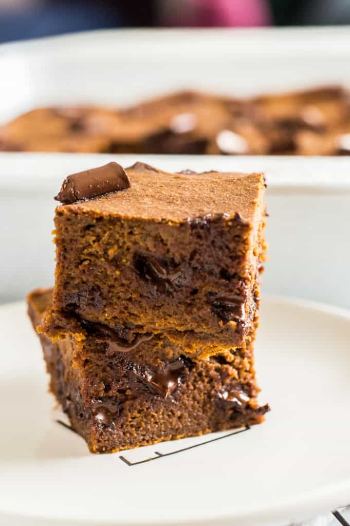 Two pumpkin brownies stacked on a plate.