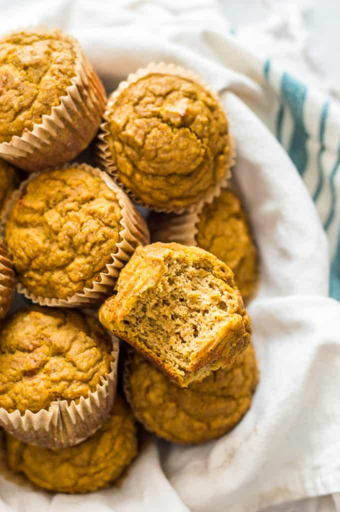 A bowl of pumpkin protein muffins. One muffin has a bite taken out of it.