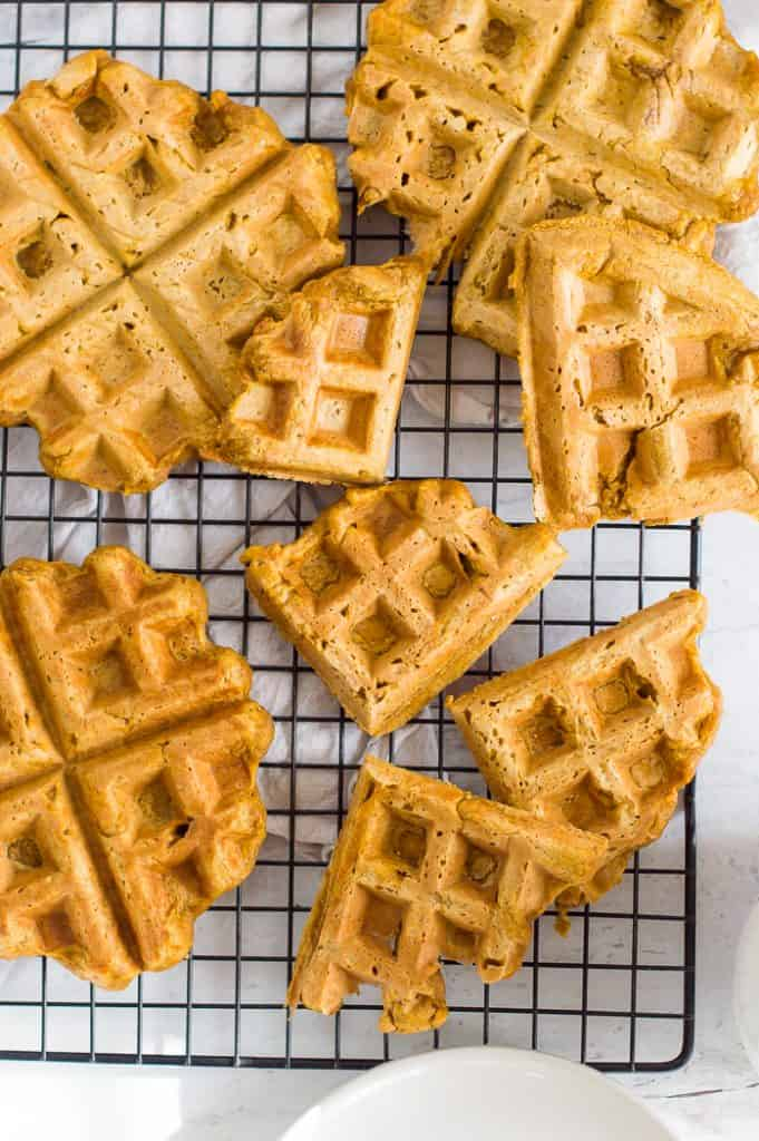 Vegan pumpkin waffles on a cooling rack on a white table.