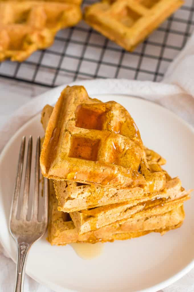 A stack of vegan pumpkin waffles on a plate with a fork. There is maple syrup is on top and there are more waffles on a cooling rack in the background.