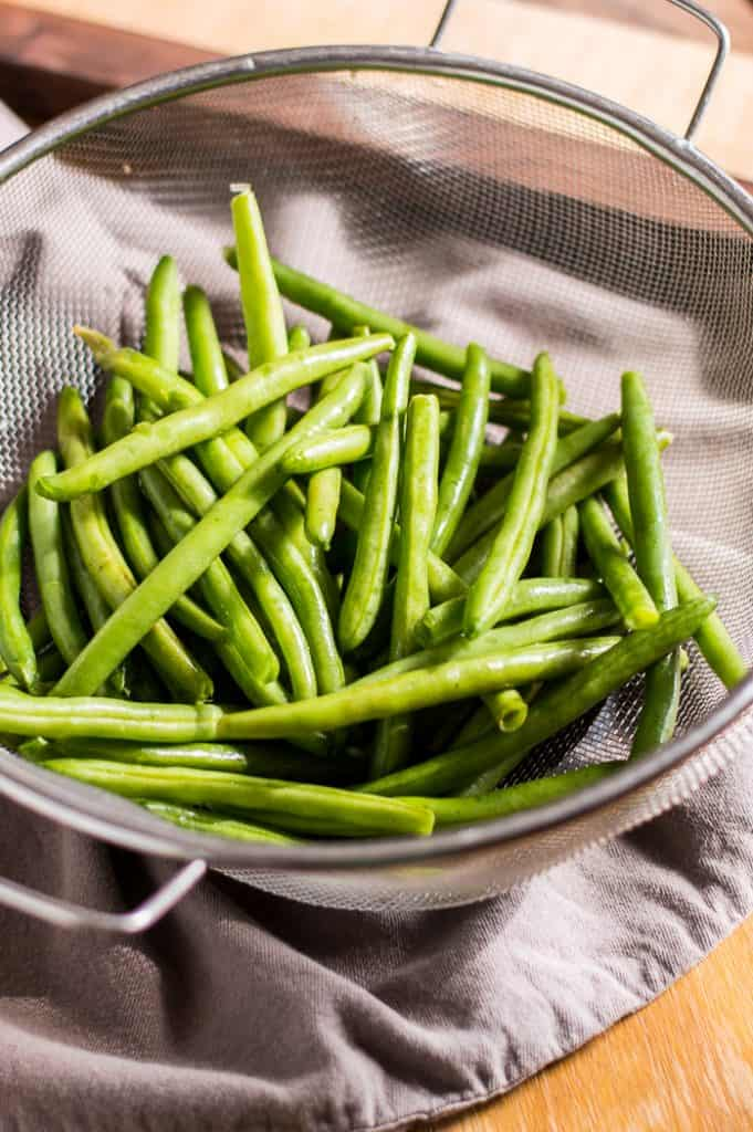 Green beans in a strainer on a table.