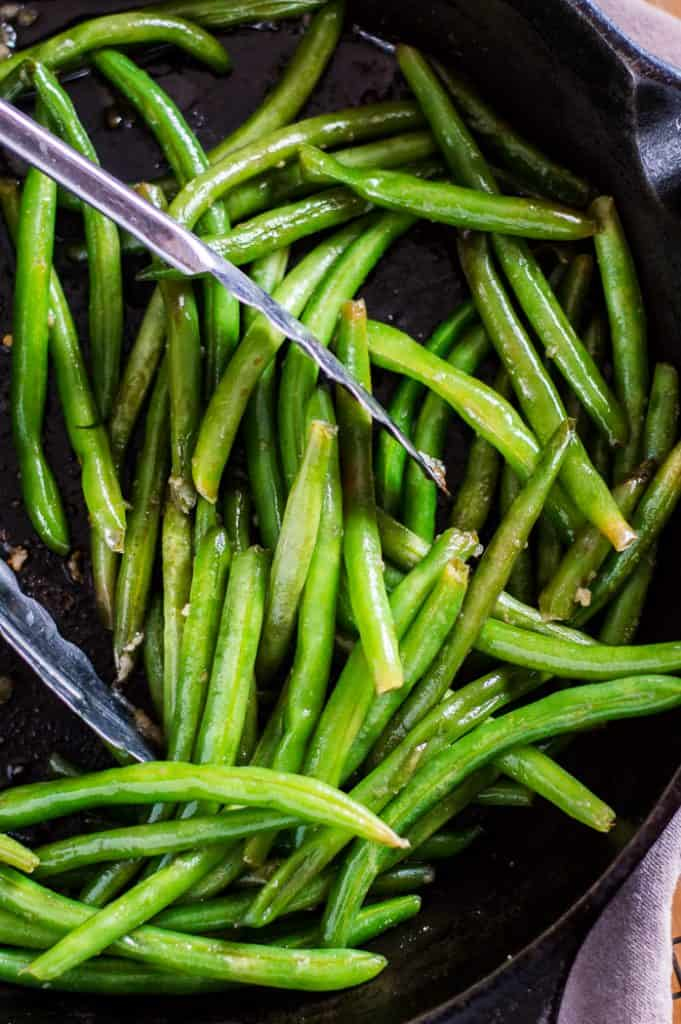 Sautéed green beans in a skillet with tongs