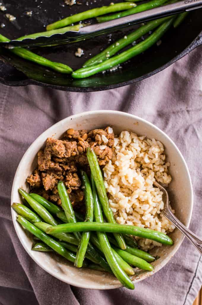 Sautéed green beans in a bowl with rice and lentils. There is a fork in the bowl