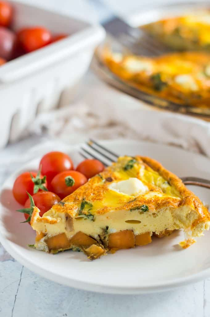 A slice of sweet potato quiche on a plate with small tomatoes. The rest of the quiche is blurred in the background.